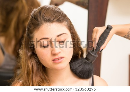 Brunette model facing camera is getting makeup and hair done by two professional stylists as they use different brushes tools.