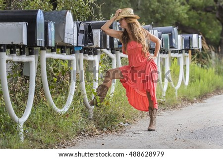 Brunette model picking up the mail in an urban environment