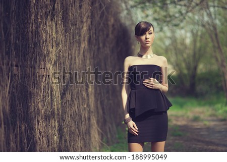 brunette model posing in short black dress - stock photo