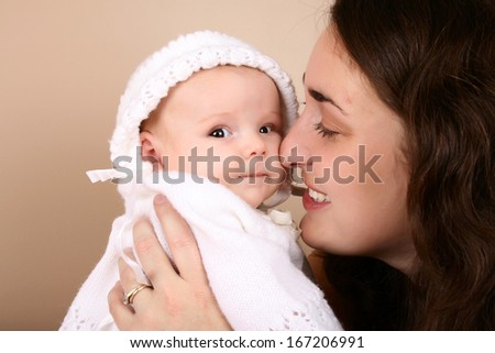 Brunette mother and baby girl dressed in white - stock photo