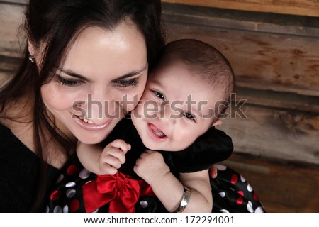 Brunette mother and baby smiling against wooden background - stock photo