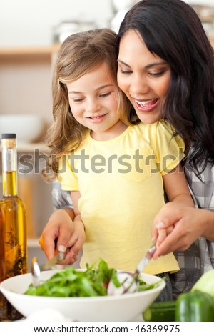 Brunette mother helping her daughter prepare salad in the kitchen - stock photo