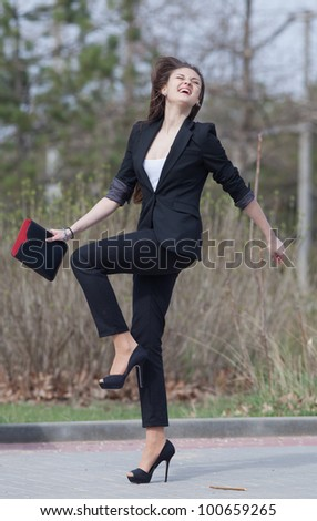 Brunette on stiletto heels in the park. Happy young woman in black suit with tablet computer in her hands runs along the park - stock photo