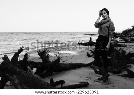 brunette on the seacoast wearing pullover, monochrome