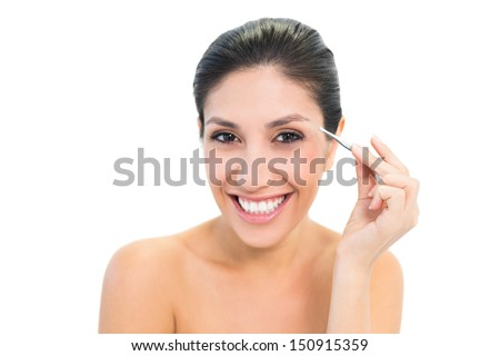 Brunette plucking her eyebrows and smiling at camera on white background