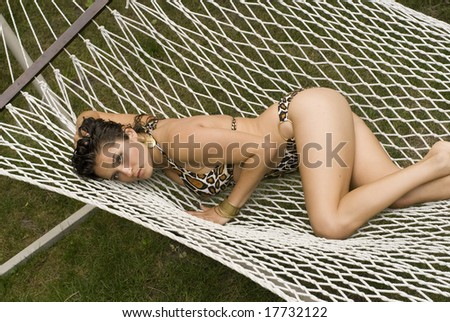 Brunette posing with her butt in the air while laying on a white hammock - stock photo