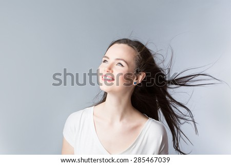 Brunette. Purposeful woman with hair in the wind.