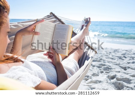 Brunette reading a book while relaxing in the hammock at the beach - stock photo