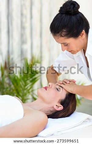 Brunette receiving forehead massage at the spa - stock photo