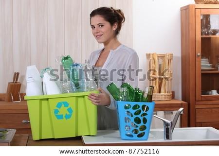Brunette recycling empty bottles - stock photo