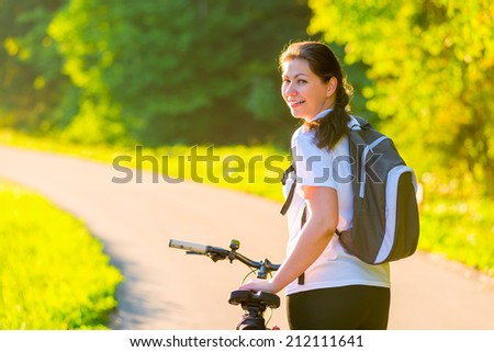 Brunette rides a bicycle on a sunny morning - stock photo