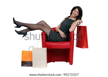 Brunette sat in chair with shopping bags - stock photo