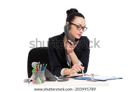 brunette secretary talking on the phone sitting over table isolated on the white  - stock photo