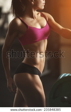 Brunette sexy fitness girl in pink sport wear with perfect body in the gym posing before training set. Part of body. Attractive fitness woman, trained female body, lifestyle portrait, caucasian model - stock photo