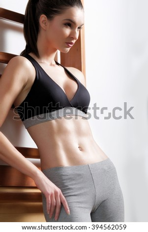 Brunette sexy fitness girl in sport wear with perfect body in the gym posing before training set - stock photo