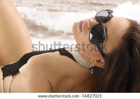 brunette sexy girl with long hair wearing a black swimsuit and sunglasses laying down on white
