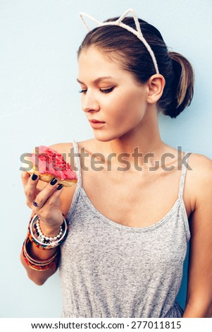 Brunette sexy woman holding tasty donut. Outdoors lifestyle portrait of pretty girl - stock photo