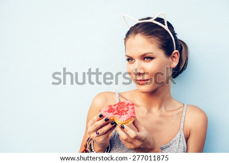 Brunette sexy woman with tasty donut. Outdoors lifestyle portrait of pretty girl - stock photo