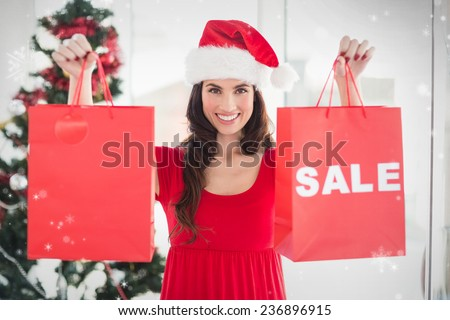 Brunette showing sale bag and shopping bag against snow falling - stock photo