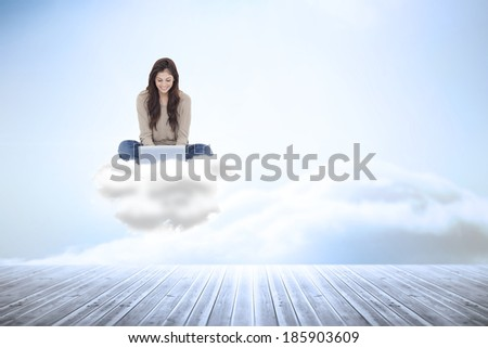 Brunette sitting on cloud using laptop against beautiful blue sky with clouds - stock photo