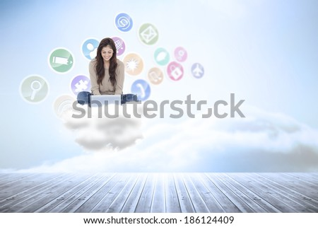 Brunette sitting on floor using laptop against beautiful blue sky with clouds - stock photo
