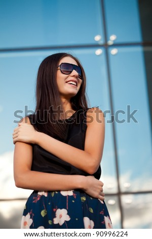 brunette smiling woman wearing sunglasses over glass wall