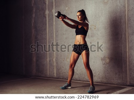 Brunette sportswoman working out her arms with a kettlebell - stock photo