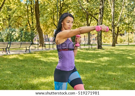 Brunette sporty female in colorful sportswear doing biceps workouts with dumbbells in a park.
