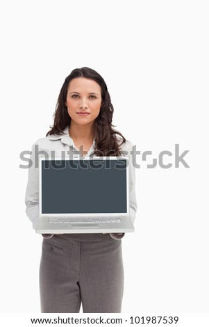 Brunette standing while showing a laptop screen against white background