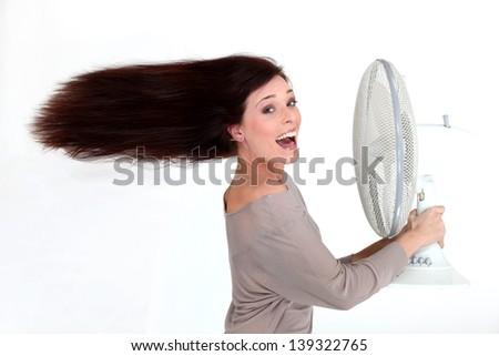 Brunette stood in front of fan - stock photo