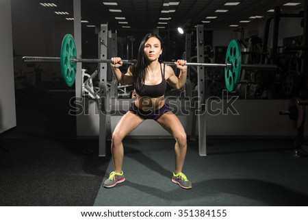 Brunette strong fitness sexy woman doing barbell squats in a gym - stock photo
