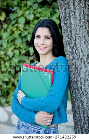 Brunette student on campus against a tree - stock photo