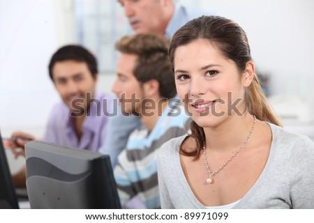 Brunette student sat next to class mates - stock photo