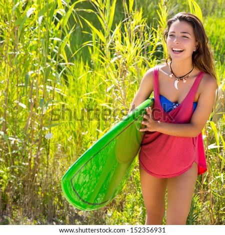 Brunette surfer girl walking in the jungle with surfboard - stock photo