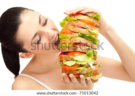 brunette taking a big bite out of huge sandwich on white background