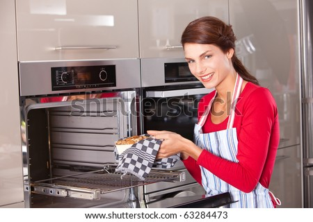 Brunette taking her freshly baked cake out of the oven - stock photo