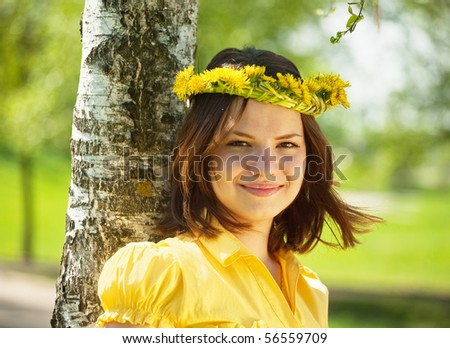 Brunette teen girl in  dandelion wreath  near birch