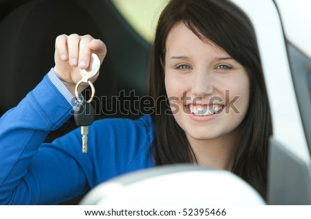Brunette teen girl sitting in her car holding keys after bying a new car - stock photo