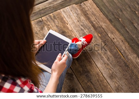 Brunette teen using a tablet pc sitting on the floor in a living room - stock photo