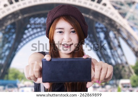 Brunette teenage girl enjoy holiday in Paris and take self picture at Eiffel Tower - stock photo