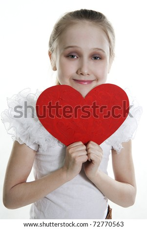 Brunette the girl has control over the big heart - a love symbol - stock photo