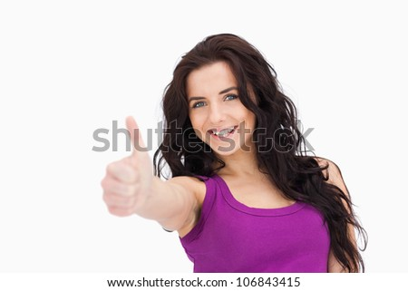 Brunette the thumb-up against white background