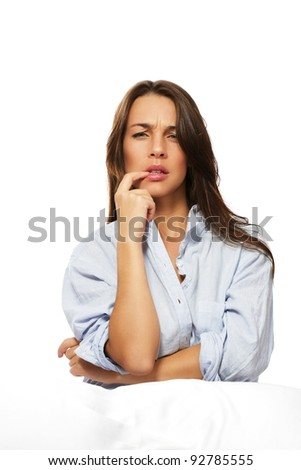brunette thinking woman sitting in bed on white background - stock photo