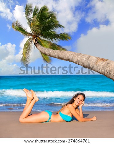 Brunette tourist lying in beach sand tanning happy in summer vacation Mexico palm tree photo mount - stock photo