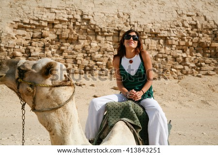 brunette tourist woman portrait sitting riding on white dromedary or arabic camel resting on desert next to Bent Pyramid in Dahshur, Egypt, Africa, for Sneferu pharaoh - stock photo