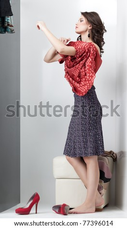 brunette trying on red dress in the mirror - stock photo