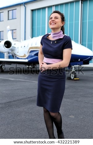 Brunette uniformed flight  attendant laughing by the small jet plane - stock photo
