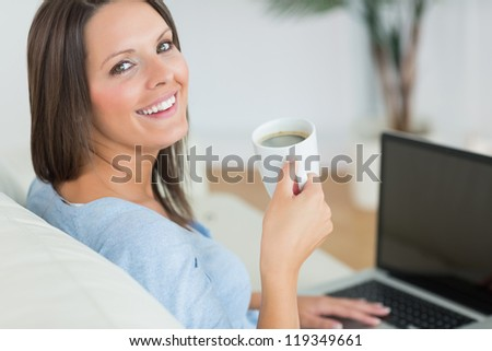 Brunette using her laptop and drinking a cup of coffee in the living room - stock photo