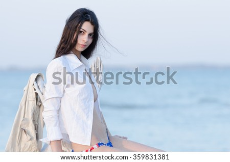 Brunette wearing open shirt and bottom bikini sitting on a washed up tree trunk by the sea, sea and horizon as background