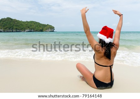 brunette wearing santa claus hat sitting on tropical beach - stock photo